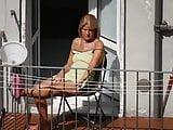 Tanned granny sunbathing on the balcony