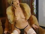 Mature in fur coat in strapon session